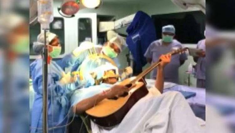 يعزف على الجيتار أثناء خضوعه لعملية جراحية بالمخ